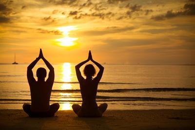 Young Couple Practicing Yoga On The Sea Beach At Sunset
