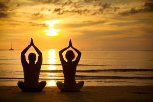 Young Couple Practicing Yoga On The Sea Beach At Sunset by De Visu