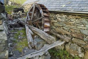 Defunct Undershot Waterwheel on Old Mill Ruin on Welsh Hillside