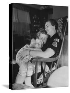 Den Mother Still in Uniform, Sleeping While Holding Her Daughter