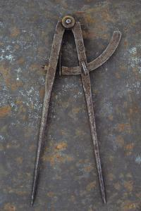 Pair of Vintage Tarnished Measuring Dividers Or Compasses Lying On Rusty Metal Sheet by Den Reader