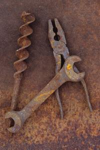 Rusty Old Double-headed Spanner Lying Next To Large Drill Bit And Rusty Pliers On Rusty Metal Sheet by Den Reader