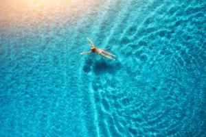 Aerial View of Swimming Woman in Mediterranean Sea at Sunset by denbelitsky