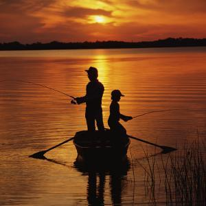 Silhouette of Father and Son Fishing at Sunset by Dennis Hallinan
