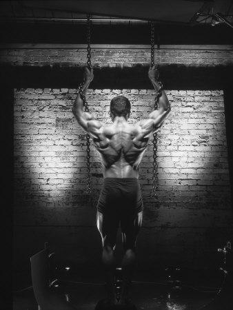 Rear View of Muscular Man Holding Chains