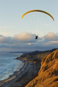 California, La Jolla, Paraglider Flying over Ocean Cliffs at Sunset. Editorial Use Only by Design Pics Inc