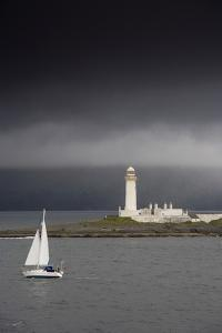 Sailboat Near a Shore with a Lighthouse; Eilean Musdile in the Firth of Lorn,Scotland by Design Pics Inc