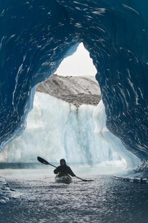Sea Kayaker Paddles Through an Ice Cave Amongst Giant Icebergs Near Bear Glacier by Design Pics Inc