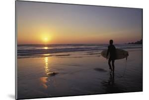 Silhouetted Surfer on Sandy Beach at Sunset by Design Pics Inc