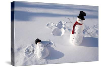 Snowmen in Forest Making Snow Angel Imprint in Snow in Late Afternoon Sunlight Alaska Winter