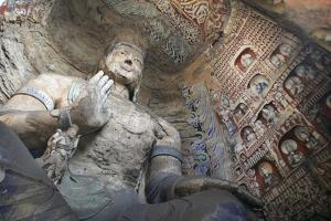 Statue and Carvings in Ancient Buddhist Temple Grotto by Design Pics Inc