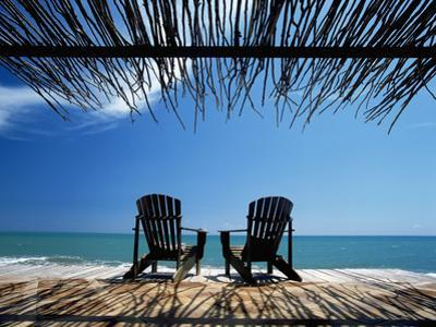 Two Chairs on Deck by Ocean Shaded by Grass Roof by Design Pics Inc