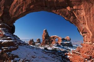 Winter Snow Covers Turret Arch Looking Through the North Window Formation at Arches National Park by Design Pics Inc
