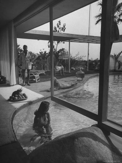 Designer Raymond Loewy Relaxing by Swimming Pool Which Runs from Outdoors Into Living Room-Peter Stackpole-Premium Photographic Print