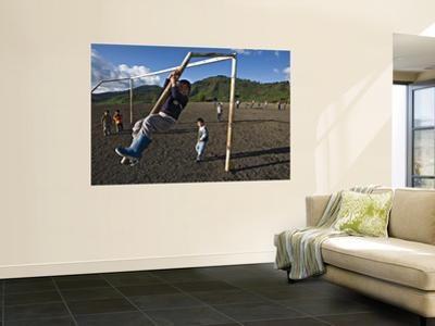 Boy Climbing Goal Post, with Corn Fields on Slopes of Acatenango Volcano in Background
