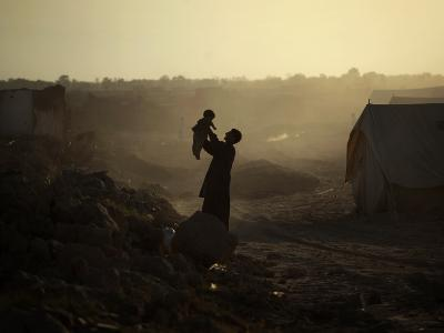 Displaced Man Holds His Baby Next to His Tent in Jalozai Refugee Camp Near Peshawar, Pakistan--Photographic Print