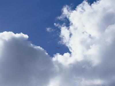 Distant Airplane in a Cloud-Filled Sky-Bill Curtsinger-Photographic Print