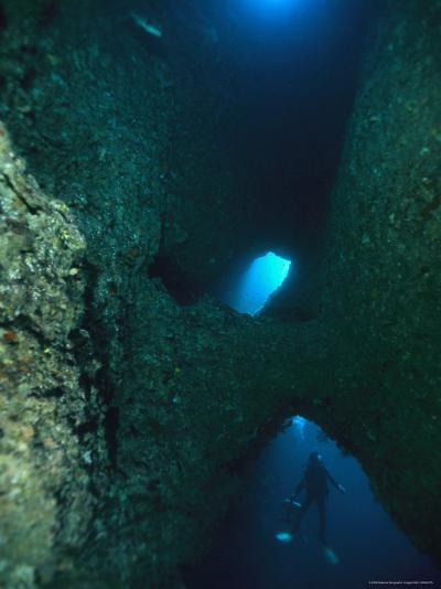 Diver Swimming Around Crevasses in a Reef Wall-Tim Laman-Photographic Print