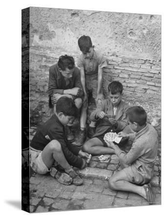 Boys Playing Cards on Steps in Town