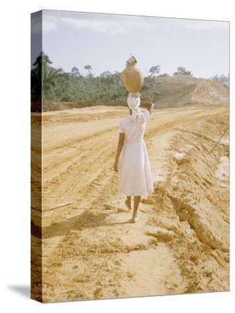 Brazilian Woman Walking Down a Sandy Road Carrying a Large Jar on Her Head