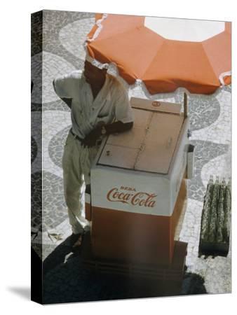 Coca-Cola Vendor Leaning on Cart with Umbrella on Mosaic Sidewalk, Copacabana Beach, Rio de Janeiro