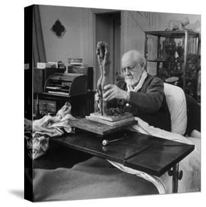 Henri Matisse Sculpting Nude Female Figure While Sitting in Bed in His Apartment by Dmitri Kessel