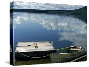 Rowboat Moored at Edge of Lake Showing Reflections of Clouds in Its Still Waters, in New England by Dmitri Kessel
