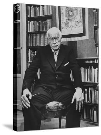 Swiss Psychiatrist Dr. Carl Jung Holding Pipe as He Sits on Chair in His Library at Home