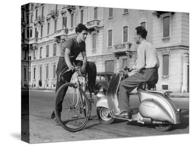 Two Men Talking in Street with Vespa Scooter and Bicycle