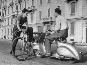 Two Men Talking in Street with Vespa Scooter and Bicycle by Dmitri Kessel