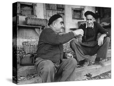 Two Older Basque Men Sitting on a Porch Toasting, as They Prepare to Drink Together