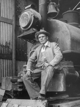 """Doby Doc"" Sitting in Front of One of the First ""Iron Horses"" in the West"