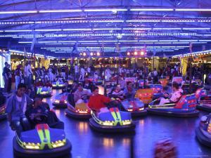 Teenagers Ride Bumper Cars under Neon Blue Lights by Dominic Bonuccelli