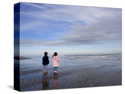 Boy Aged Four and Girl Aged Three on a Black Volcanic Sand Beach in Manawatu, New Zealand