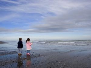 Boy Aged Four and Girl Aged Three on a Black Volcanic Sand Beach in Manawatu, New Zealand by Don Smith
