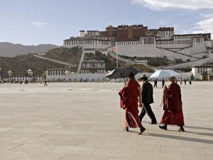 Monks Carrying Umbrellas to Shield Against the Sun, in Front of the Potala Palace, Tibet by Don Smith