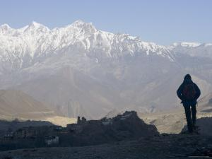 Trekker at Dawn Looking out Over the Old Fortified Village of Jharkot on the Annapurna Circuit Trek by Don Smith