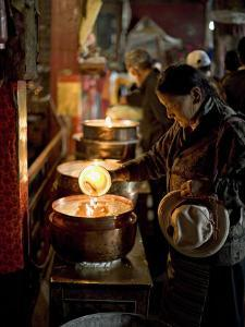 Woman Adding the Melting Yak Butter from Her Lamp to Those of the Temple, Bharkor, Tibet by Don Smith