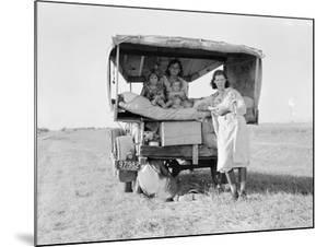 Destitute Texan family leave their home to seek work in Arkansas cotton fields, 1936 by Dorothea Lange