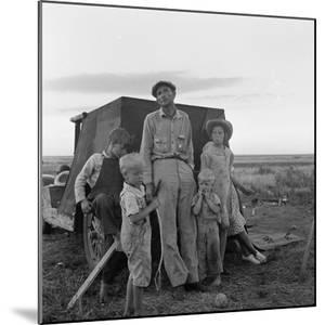 Migrant farm labourer with his children on the road in Texas, 1938 by Dorothea Lange