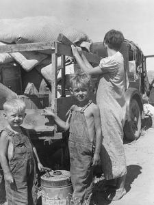 Part of an impoverished family of nine from Iowa on a New Mexico highway, 1936 by Dorothea Lange