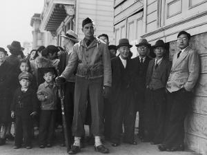 Soldier Standing Guard of Japanese American Citizens Awaiting Transport to Relocation Camps by Dorothea Lange