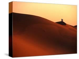Couple on Dunes in the Erg Oriental Sand Sea, Ghadhames, Libya by Doug McKinlay