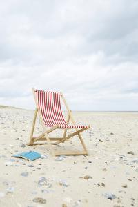 Deck Chair with Book on Sand at Beach. by Dougal Waters