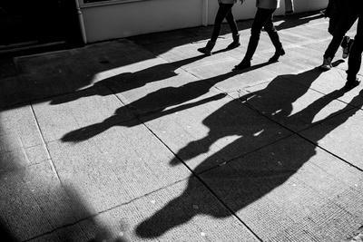 Shadows of Four Walking Pedestrians Projected on the Sidewalk