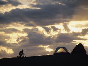 A Mountain Biker Cycles Toward Tents at a Campsite by Dugald Bremner