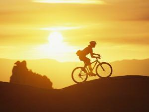 A Woman Rides Her Bike in the Sunset with Rock Cliffs in the Background by Dugald Bremner