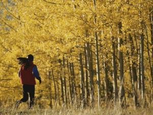 Woman Running in Field by Aspen Trees by Dugald Bremner