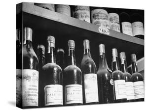 Dust-Covered Wine and Brandy Bottles Standing on Racks in a Wine Cellar