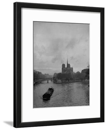 River Barge Churning up the Seine Past Notre Dame Cathedral on a Gloomy Winter Day